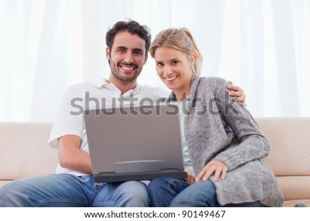 Young couple using a notebook in their living room - stock photo