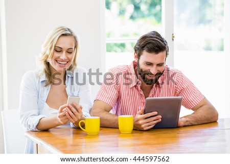 Young couple using digital tablet and mobile phone at home - stock photo
