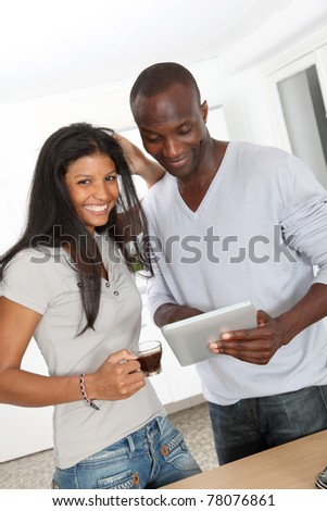 Young couple using electronic pad in kitchen - stock photo