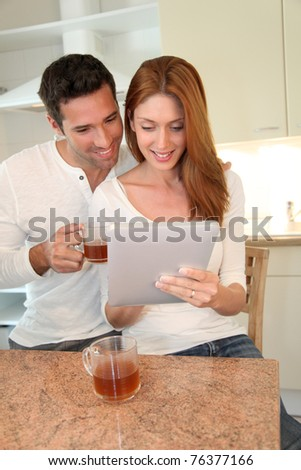 Young couple using electronic tablet in home kitchen - stock photo