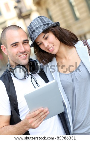 Young couple using electronic tablet in town - stock photo