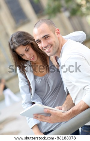 Young couple using electronic tablet in town