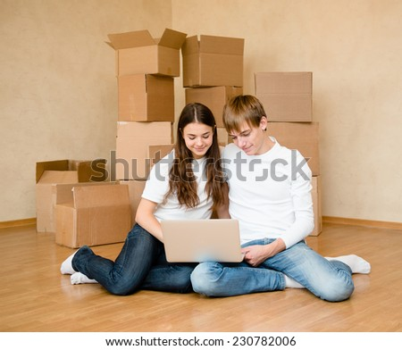 young couple using laptop in their new home - stock photo