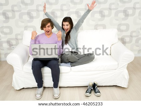 Young couple using laptop on couch - stock photo