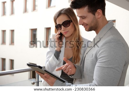 Young couple using mobile and tablet in corridor. - stock photo