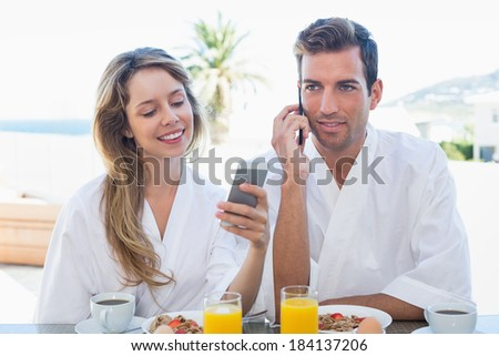 Young couple using mobile phones while having breakfast at home - stock photo