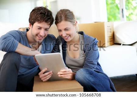 Young couple using tablet to find transport company