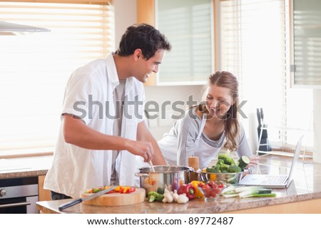 Young couple using the internet to look up recipe - stock photo
