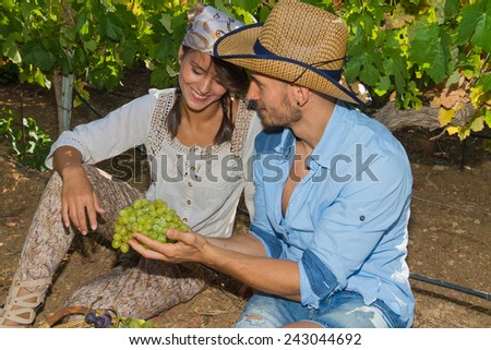 Young couple, vine growers, enjoy eating grapes while seated on the ground under the vines. - stock photo