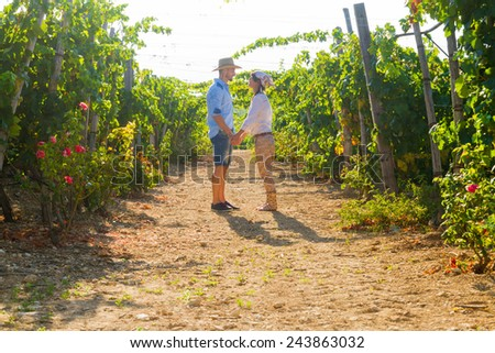 Young couple, vine growers, hugging and kissing in the  grape vines early in the morning. - stock photo