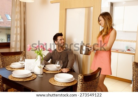 Young couple waiting for friends at home to have dinner together. Woman serving soup. - stock photo