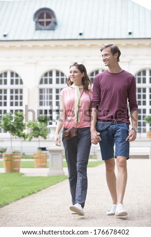 Young couple walking against buildings - stock photo