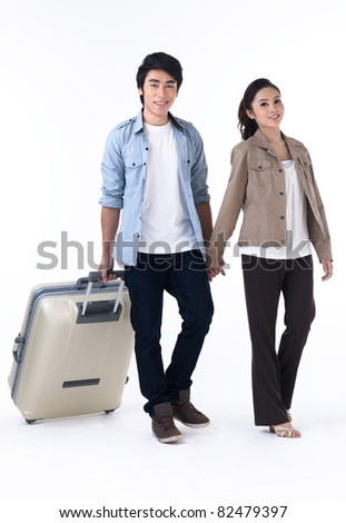 Young couple walking and pulling a luggage - stock photo