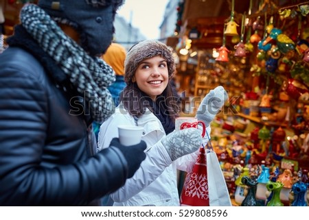 Young couple walking at christmas fair on the street, drinking hot drinks, smiling.