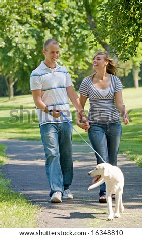 Young Couple Walking Dog - stock photo