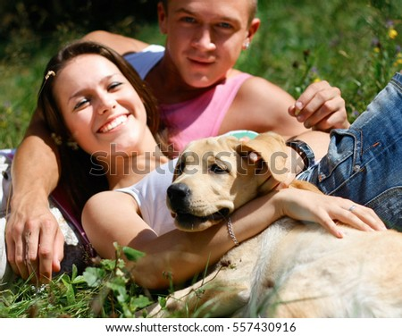 Young couple walking dog on the nature