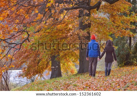 Young couple walking in a park in autumn gold - stock photo