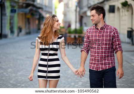 Young couple walking in the old part of town - stock photo