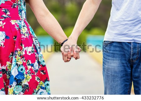 young couple walking in the park and holding hands