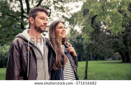 Young couple walking in the park and hugging each other. Concept about relationship and couples - stock photo