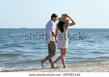 Young couple walking on beach - stock photo