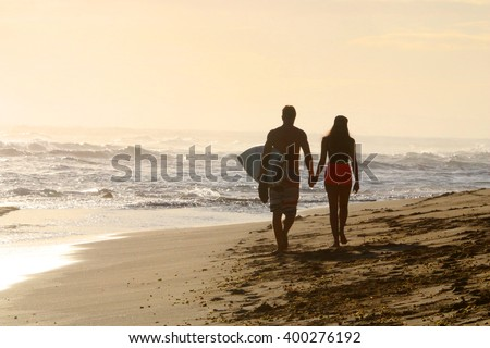 Young couple walking on the beach goes to surf - stock photo