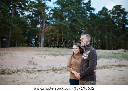 young couple walking on the rocky beach