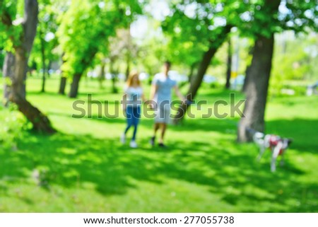 stock-photo-young-couple-walking-the-dog