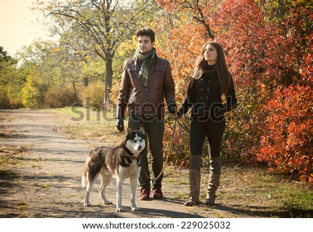 Young couple walking their husky dog in autumn countryside - stock photo