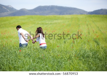 Young couple walking through green field.