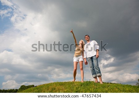 Young couple walking through summer lawn - stock photo