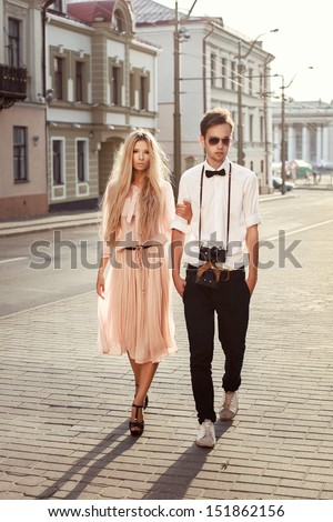 Young couple walking up the street. Retro vintage fashion portrait in summer - stock photo