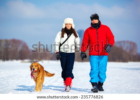 Young couple walking with dog. Cold winter season and snowfield. - stock photo