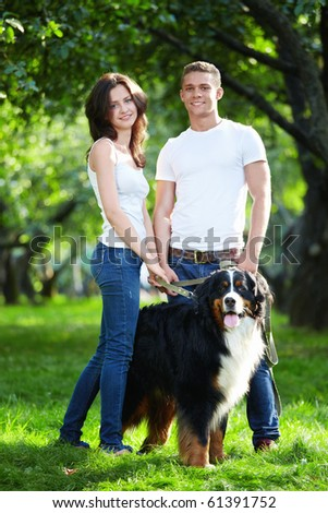 Young couple walking with dog in park - stock photo