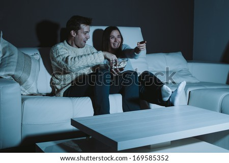 Young couple watching a comedy on TV - stock photo