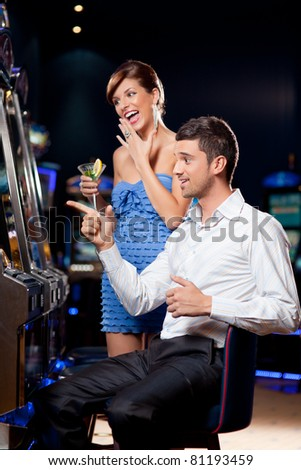 young couple watching exiting, winning at the slot machine - stock photo