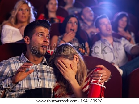 Young couple watching horror movie in cinema, girl turning her head away with fear. - stock photo