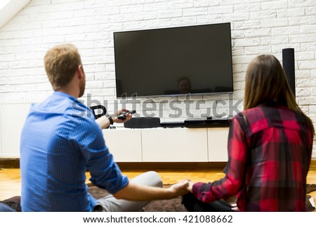 Young couple watching television sitting comfortably on floor and holding the remote control - stock photo