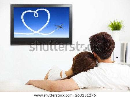 young couple watching the  tv show in living room - stock photo