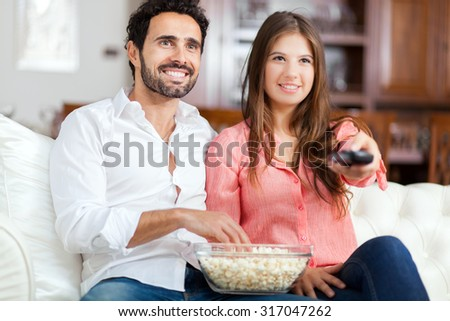 Young couple watching tv and eating pop-corn - stock photo