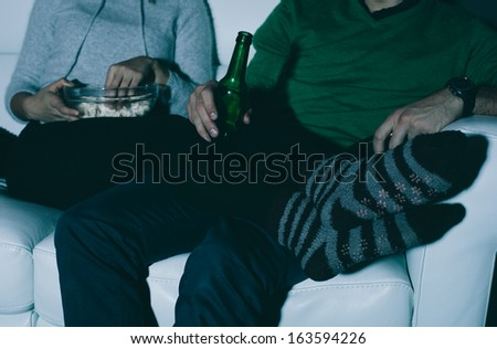 Young couple watching TV at home - stock photo