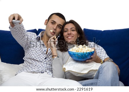 young couple watching tv at home and laughing - stock photo