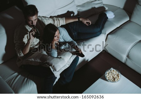 Young couple watching TV at home at night - stock photo