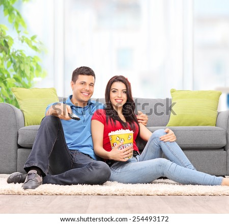 Young couple watching TV seated on the floor at home shot with a tilt and shift lens - stock photo