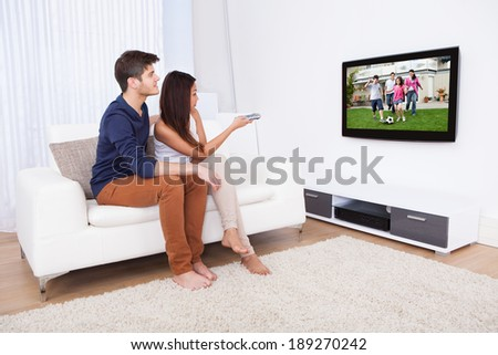 Young couple watching TV while sitting on sofa in living room at home