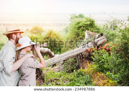 Young couple watching with binoculars african leopard.Copy space, lens flare - stock photo