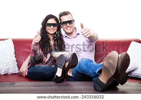 Young couple wearing 3D glasses and preparing to watch a 3D movie  - stock photo