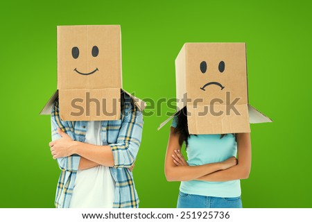 Young couple wearing sad face boxes over head against green vignette - stock photo