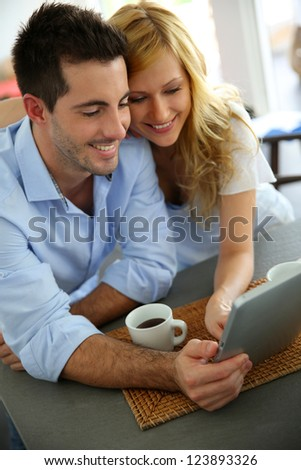 Young couple websurfing with tablet in home kitchen - stock photo