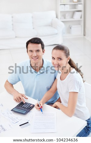 Young couple with a calculator at home - stock photo